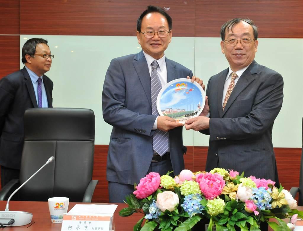 金大校長黃奇(右)致贈來訪台商紀念盤,由「台企聯」榮譽總會長張漢文(中)代表接受。(李金生攝)