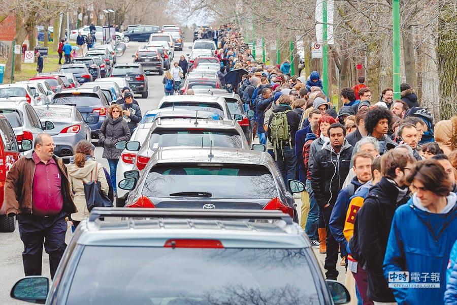 大排長龍  大批法國僑民22日在加拿大第二大城蒙特婁的史坦尼斯拉學院外排隊,等候進入設在該校的法國總統大選投票所投票。(路透)