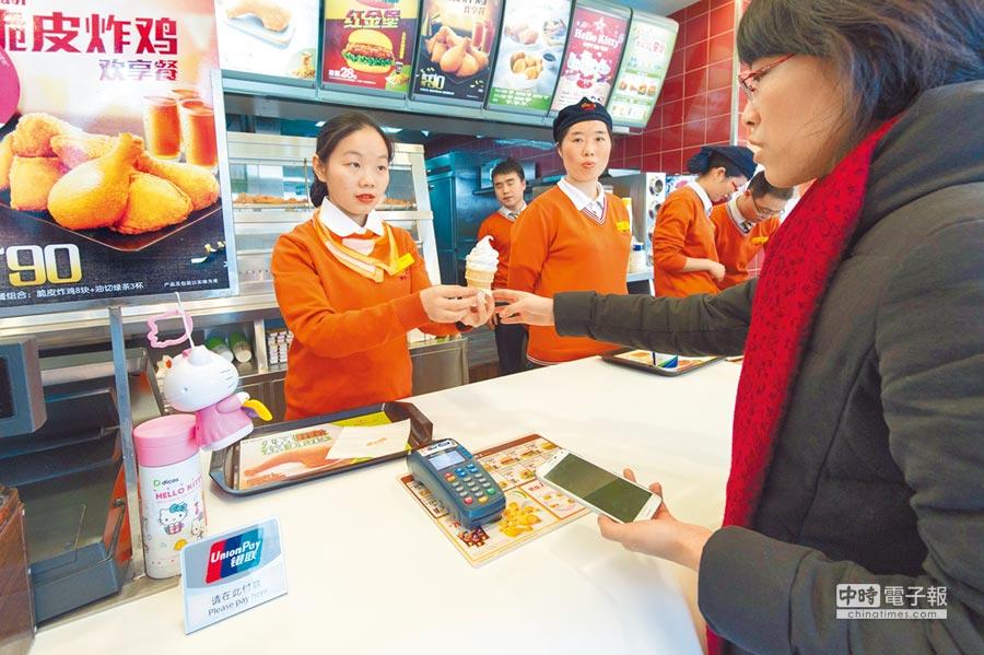 成都民眾用綁定銀行卡的手機通過雲閃付購買食品。(新華社)