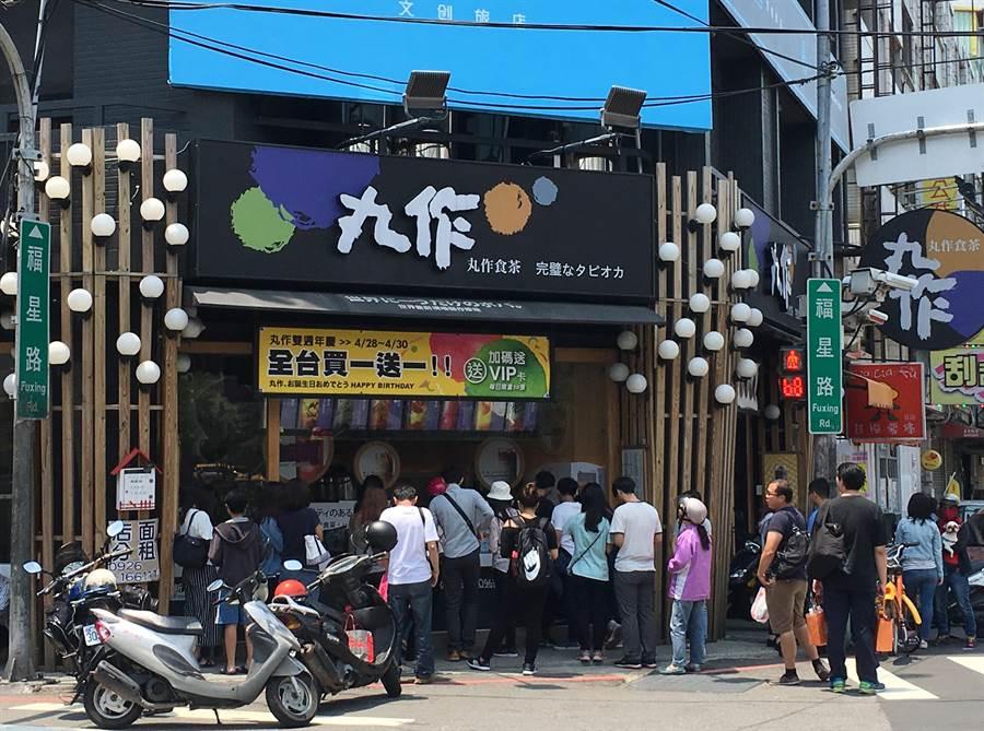 丸作茶飲是近年相當火紅的手搖飲店,其店門舖形象都以兩側如樹的木條再點綴圓形的白色燈罩。(馮惠宜攝)