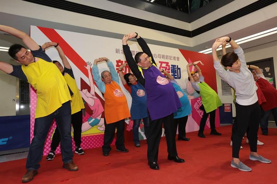 新北市政府7日上午在中和國民運動中心舉行「新北好孕動」聯合記者會,副市長侯友宜(中)穿孕婦體驗裝進行暖身。(葉書宏翻攝)