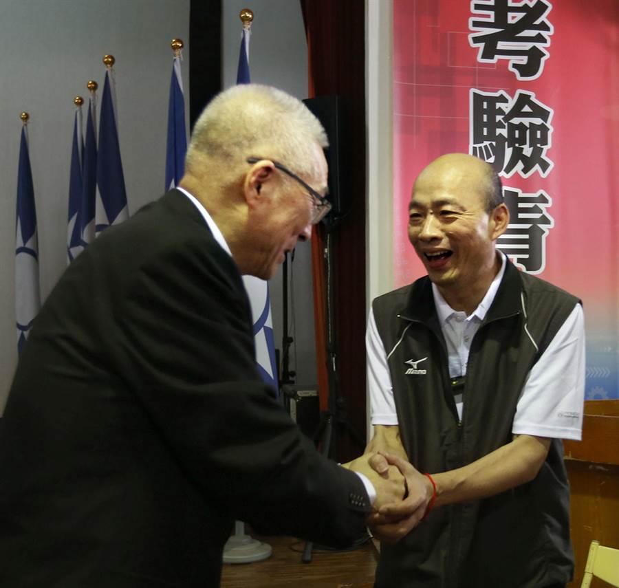 國民黨主席候選人高屏區政見會7日在鳳山舉行,其中兩位先後上台發言的國民黨主席候選人吳敦義(左)和韓國瑜(右)相互握手致意。(王錦河攝)