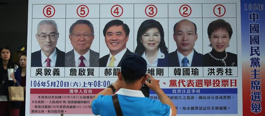 國民黨主席候選人高屏區政見會7日在鳳山舉行,6位候選人輪流上台發表政見爭取支持。1位男子在6位國民黨主席候選人看板前觀看拍照。(王錦河攝)