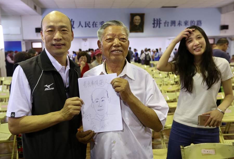 國民黨主席候選人高屏區政見會7日在鳳山舉行,1位年長支持者用筆素描韓國瑜(左)並與他合影,另1位年輕女子等在一旁也要與他合影。(王錦河攝)