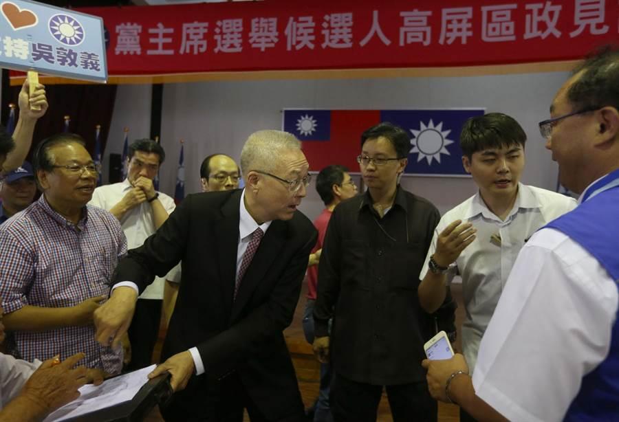 國民黨主席候選人吳敦義(中)發言後支持者趨前要求簽名,另1位候選人韓國瑜準備上台發言,吳見狀立即離開現場並和韓國瑜握手致意。(王錦河攝)
