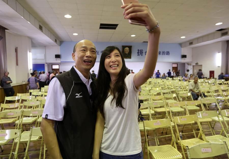 1位年輕女子用手機和國民黨主席候選人韓國瑜(左)在鳳山自拍合影。(王錦河攝)
