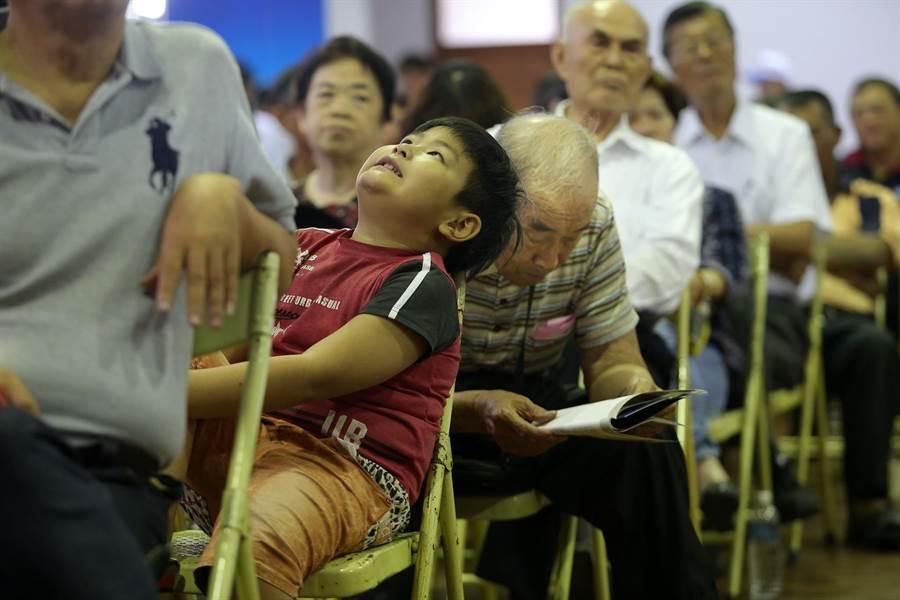 國民黨主席6位候選人高屏政見會7日在鳳山舉行,吸引不少黨員和支持者聆聽,1位跟隨家人到場的小弟弟在一群年長者中格外醒目。(王錦河攝)
