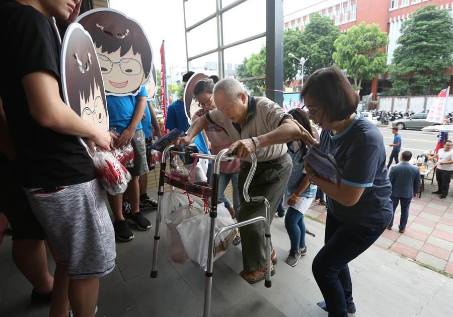 國民黨主席6位候選人高屏政見會7日在鳳山舉行,1位行動不便的老伯在工作人員攙扶下爬樓梯進入會場。(王錦河攝)