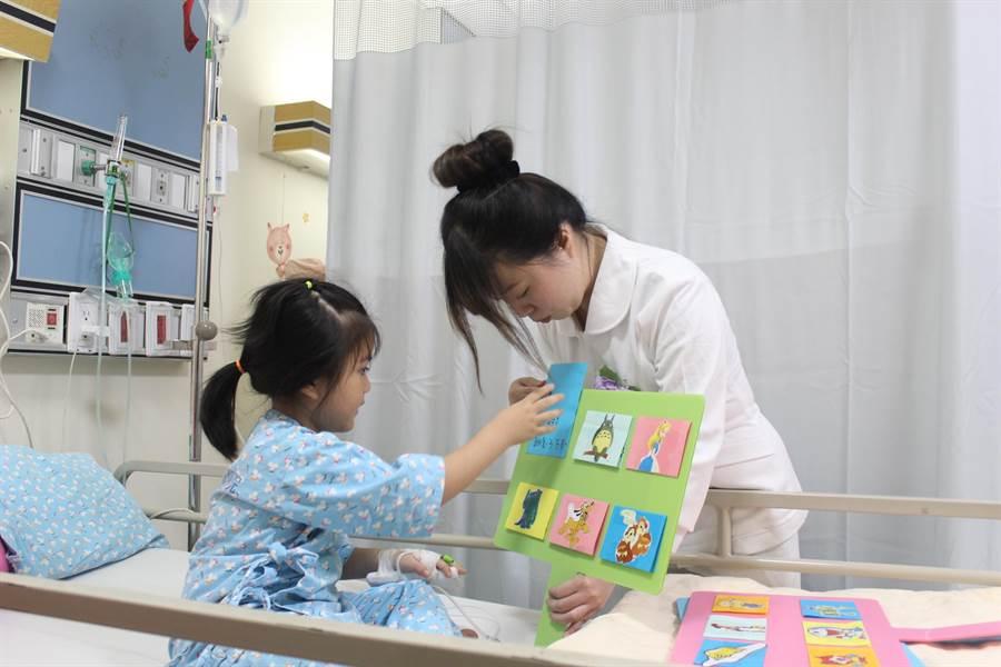 為恭醫院兒科病房護理師張琇祺運用「治療遊戲」,透過和兒童遊戲方式帶入治療,讓病童願意接受治療。(黎薇攝)