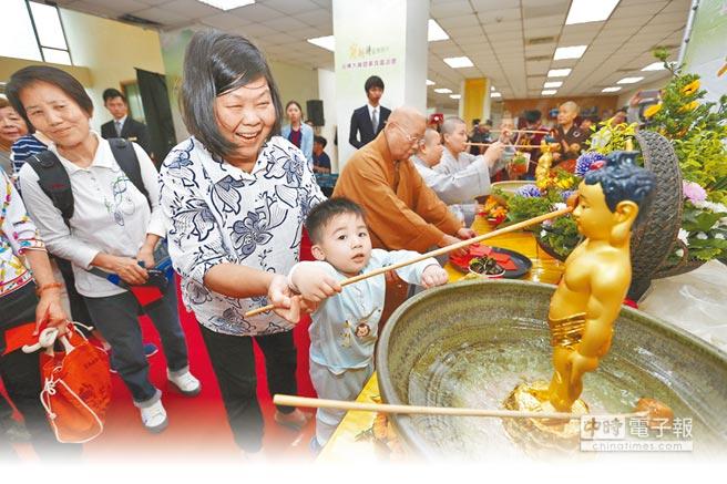 玄奘大學9日舉辦浴佛節活動,吸引不少親子參加禮佛。(徐養齡攝)