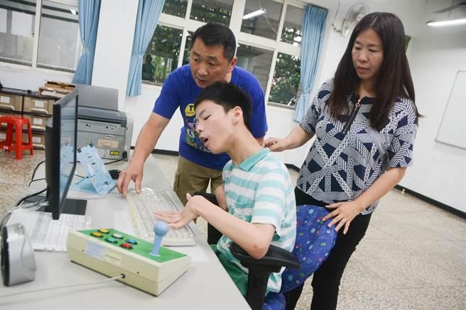腦性麻痺考生蔡東霖在父母陪伴下,前往高雄高商特殊考場事先檢視應試用具。(林宏聰攝)