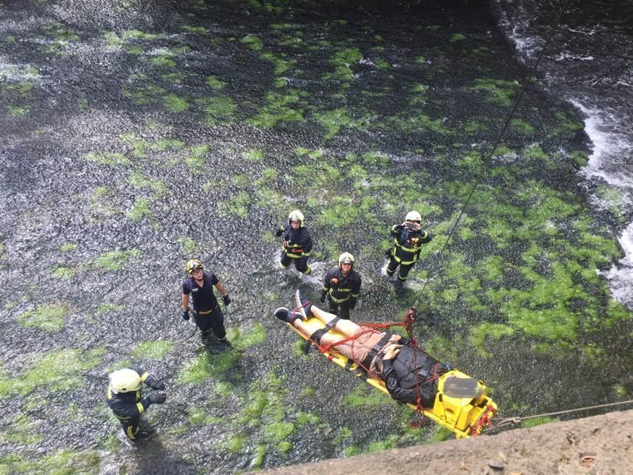 一名男子今天上午橫躺在西屯區環河路旁的大排水溝,消防人員動員搶救。(盧金足翻攝)