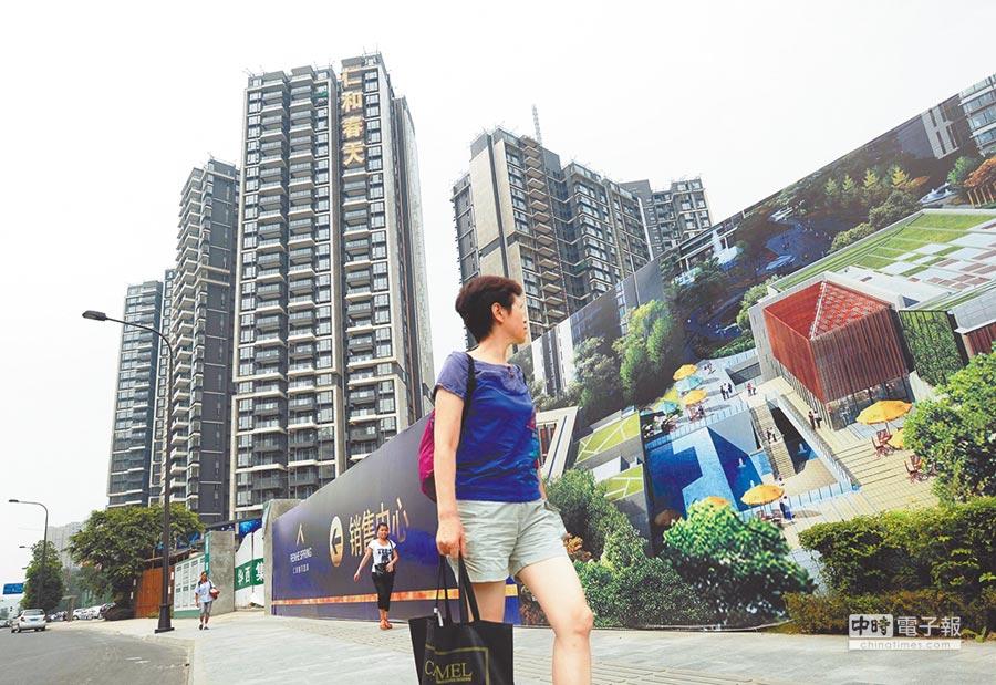 行人從成都市區的一處商業樓盤前走過。(新華社)