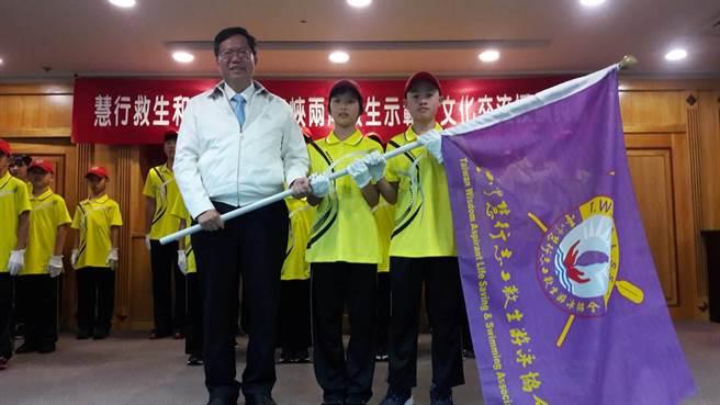 桃園市長鄭文燦授旗給即將出訪的慧行救生和平小天使們。(林郁平翻攝)