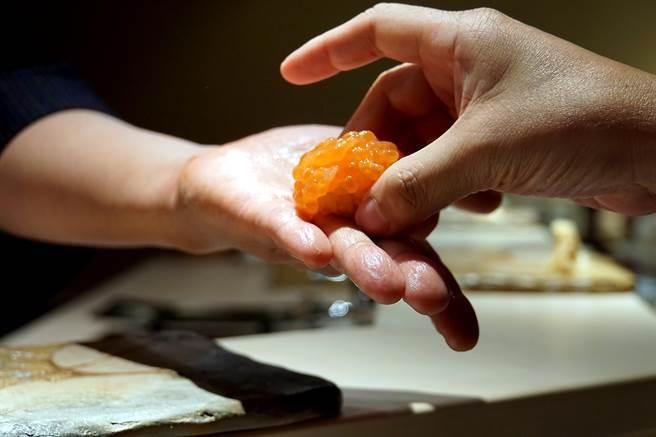 北海道鮭卵顏色搶眼、味道極鮮甜,為了避免弄破,足立浩正將握壽司捏好後即用手遞給客人享用。(圖/姚舜攝)