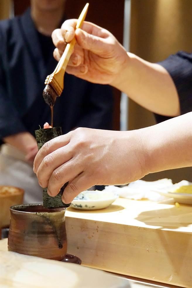 足立浩正包的〈鮭魚生捲〉是細長形,包好後並會淋醬汁提味,形狀味道與「甜筒形手捲」都不一樣。(圖/姚舜攝)