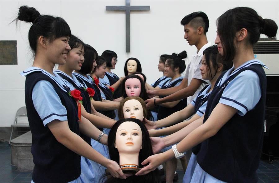 長榮女中美容科與時尚造型科畢業典禮有人頭交接,學長姐將美髮假頭遞給學弟妹,象徵傳承。(程炳璋攝)