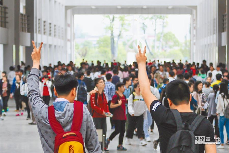 江蘇兩位考生擺出勝利手勢進入考場。(新華社)