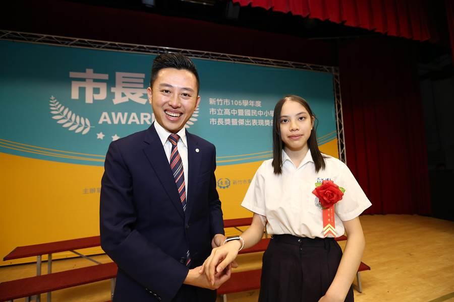 新竹市三民國中畢業生方語珩(右)不向病魔低頭,以堅強意志力積極上進,10日拿下傑出表現獎,市長林智堅(左)特別送給她健康手環。(徐養齡攝)