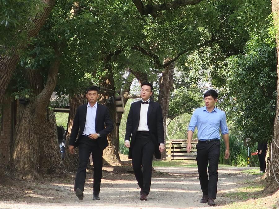 新郎官林飛帆(中)穿著黑色燕尾服步出婚宴會場接受媒體採訪,太陽花學院五虎將成員中的三人難得再同框。(謝瓊雲攝)