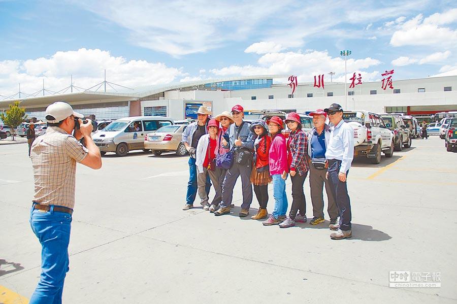 在西藏拉薩機場前合影的台灣遊客。(記者李鋅銅攝)