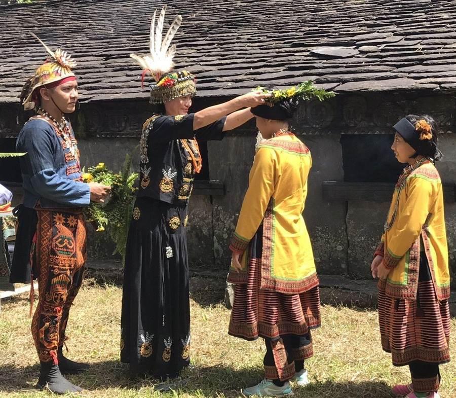 武潭國小佳平分校舉辦舊部落尋根之旅,中高年級學生回到舊部落,大公主劉秀珍為學生戴上花環。(潘建志攝)