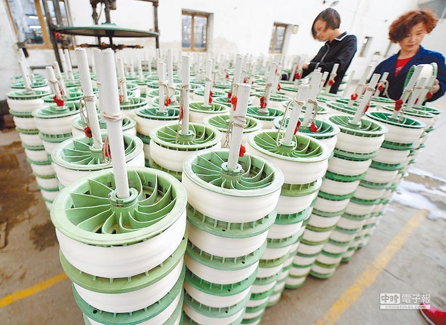 5月13日,兩名女工在湖州浙絲二廠的浸漬車間裡查看絲品。(新華社)