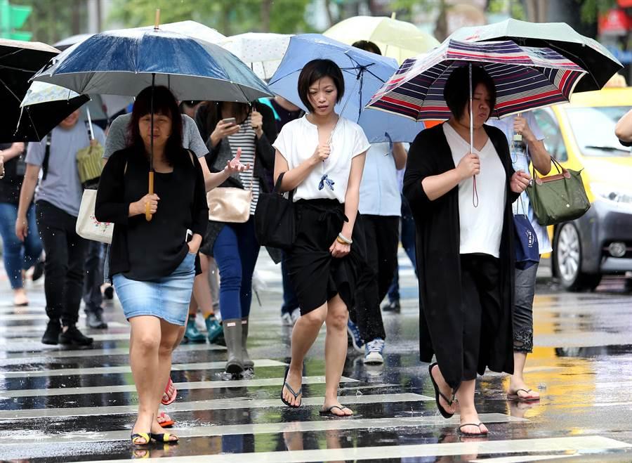 第2波梅雨鋒面14日起影響台灣,各地將長達一周雨勢不斷;北市內科的上班族換上夾腳拖鞋外出購買午餐,免去正式鞋款遭大雨淋溼的窘境。(黃世麒攝)
