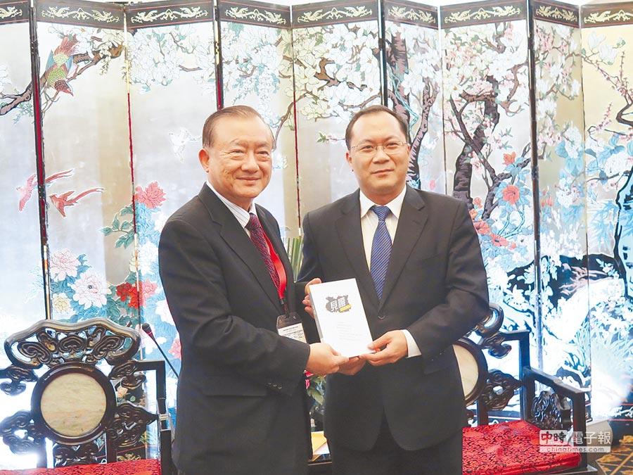 前經濟部長尹啟銘(左)贈書予廣州市委常委盧一先。(記者陳曼儂攝)