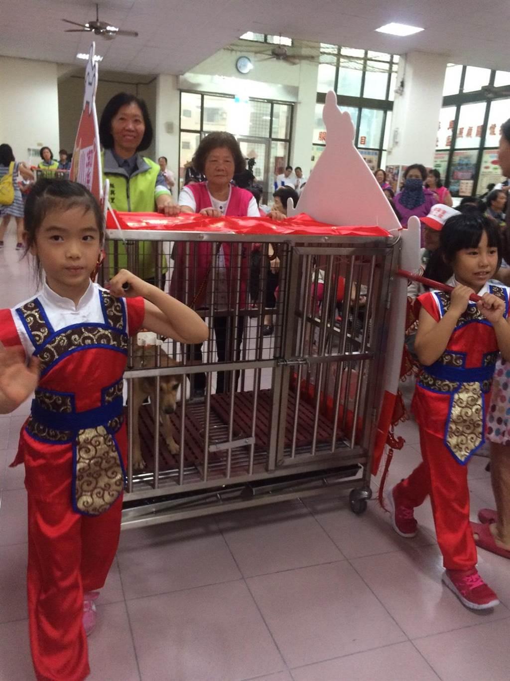 振興社區將狗籠打造成花轎,從動保處迎娶三隻流浪犬進門。(程炳璋攝)