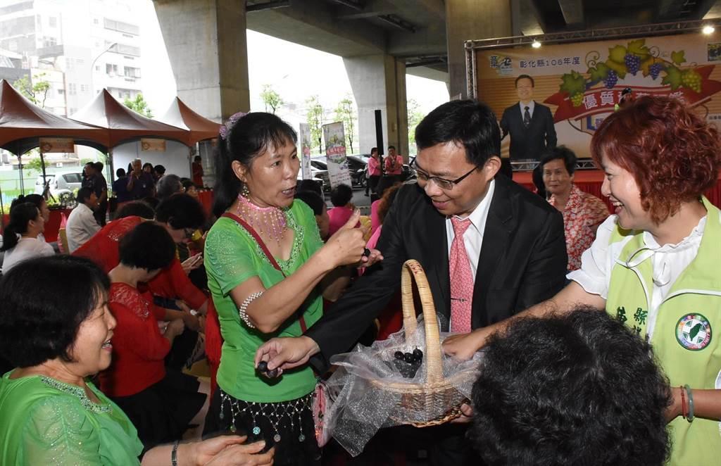 彰化縣副縣長林明裕與民眾分享葡萄酸酸甜甜的好滋味。(鐘武達攝)