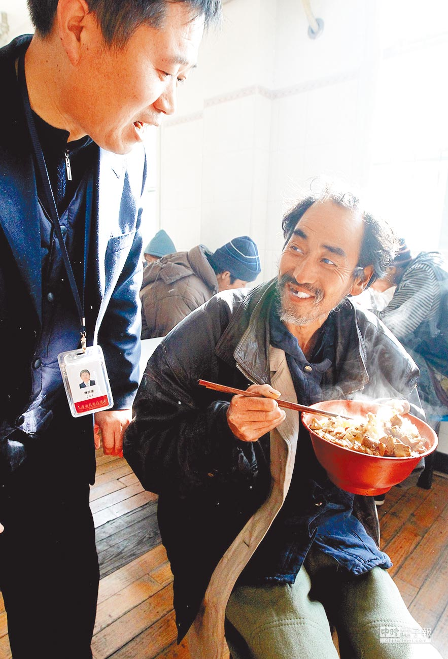來自浙江溫州的流浪漢(右)在上海救助管理站吃到了幾天來的第一頓熱飯。(新華社資料照片)