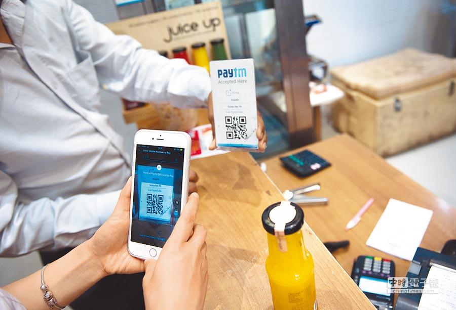 4月12日,民眾在印度新德里一家店掃二維碼付款。(新華社)