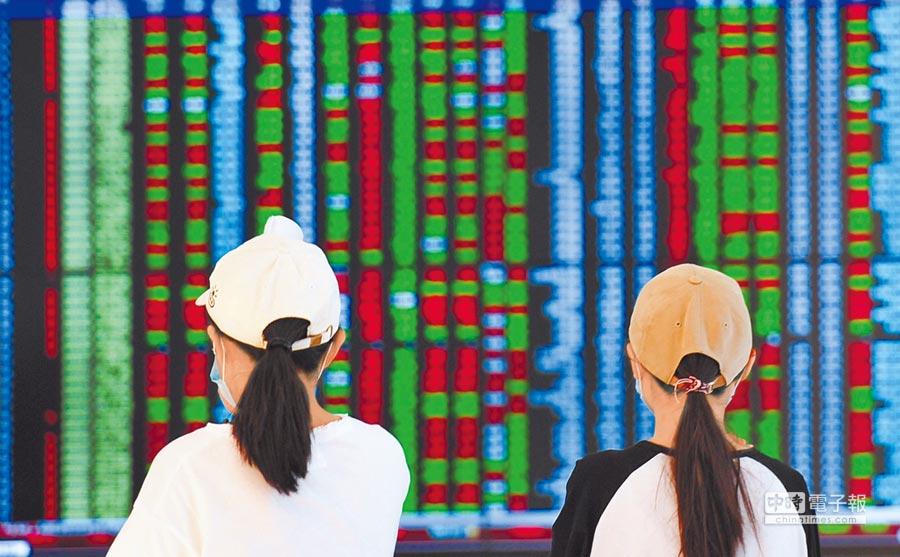遼寧瀋陽市民14日從股票大盤前經過。(中新社)