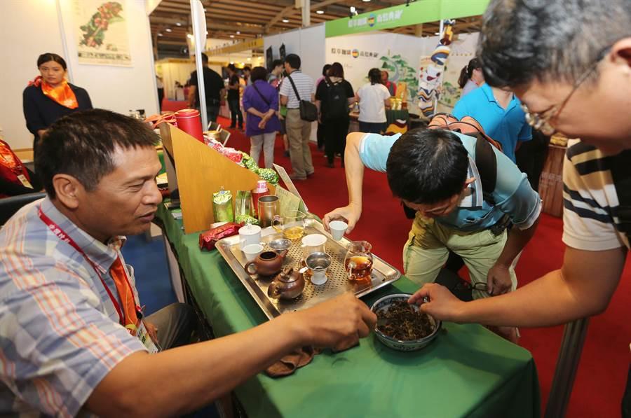 2017台中茶酒咖啡展,今日起在台中中時國際會展中心盛大登場,一業者攤位,消費者低頭仔細研究茶葉形狀,此次展期全程免費進場,優良業者齊聚,讓消費者一次逛個足夠。(黃國峰攝)
