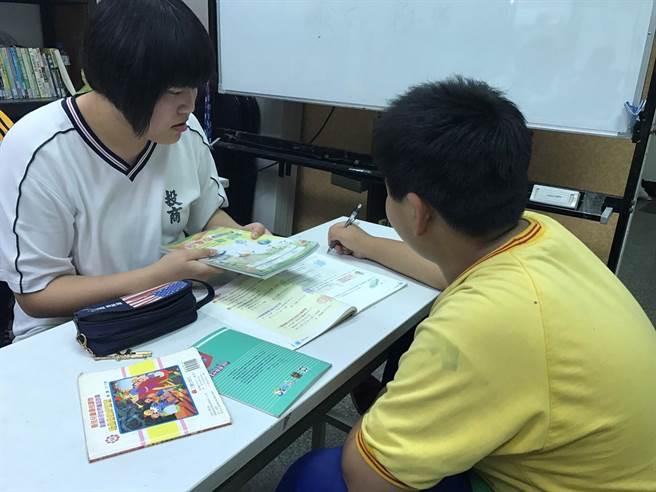南投高商學生邱詩婷(左)為夜光天使進行課後輔導。(教育部提供)