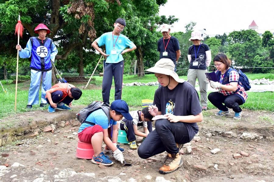 在國立成功大學考古學研究所人員的引領下,參與的大小朋友,在考古探坑親自進行挖掘,體驗考古。(文化局提供)