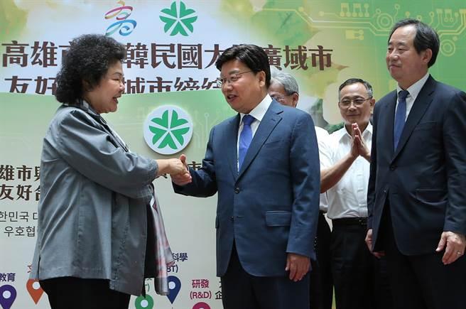 高雄市長陳菊(左)和韓國大田廣域市長權善宅(中)簽署友好合作城市協議書後相互握手致意。(王錦河攝)