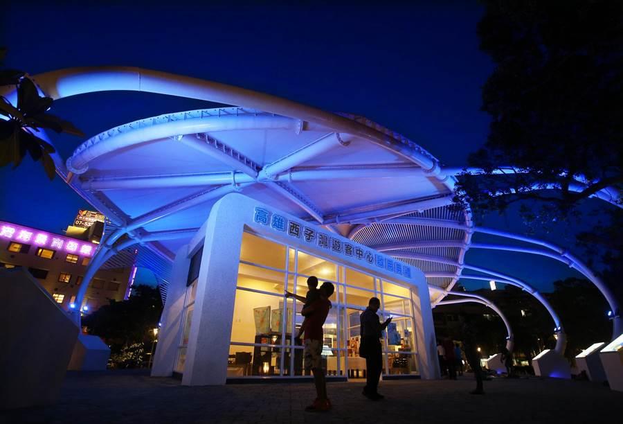 位在高雄哨船頭公園的西子灣遊客中心正式啟用,橢圓美學建築外觀採用鋼結構與薄膜屋頂等綠建築設計,傍晚 magic hour 魔術時刻呈現絢麗的湛藍色夜空,輝映多彩燈光變幻的遊客中心,吸引民眾參觀。(王錦河攝)