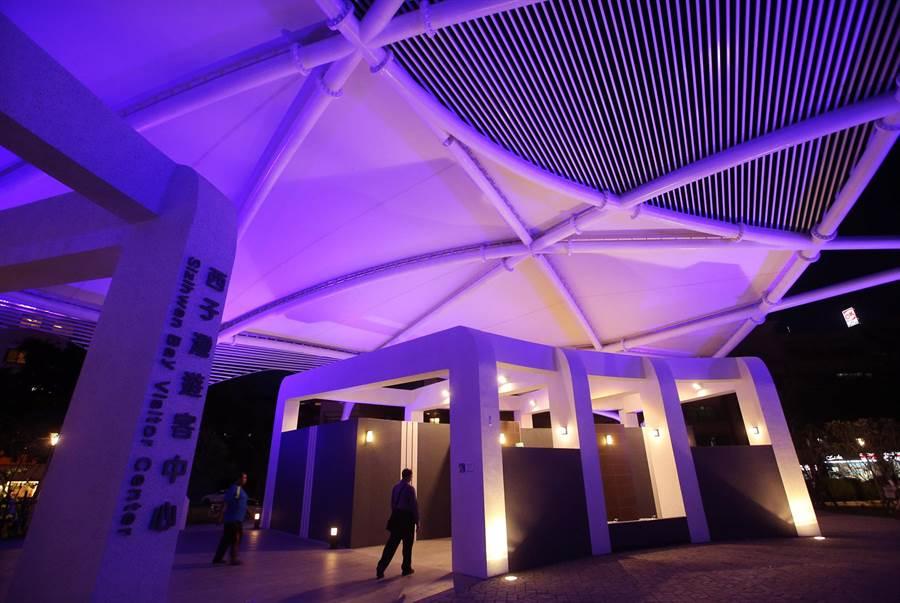 西子灣遊客中心正式啟用,橢圓美學建築外觀採用鋼結構與薄膜屋頂等綠建築設計,傍晚呈現多彩燈光變幻,遊客中心旁是男女洗手間(中)。(王錦河攝)