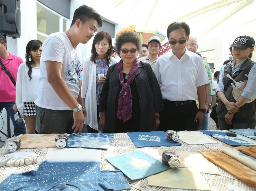 高雄市長陳菊(中)在觀光局長曾姿雯(中偏左)、立委李昆澤(右二)等人士陪同下參觀每周六日在西子灣遊客中心旁舉辦的戶外市集,眾人正參觀手工染製衣物。(王錦河攝)
