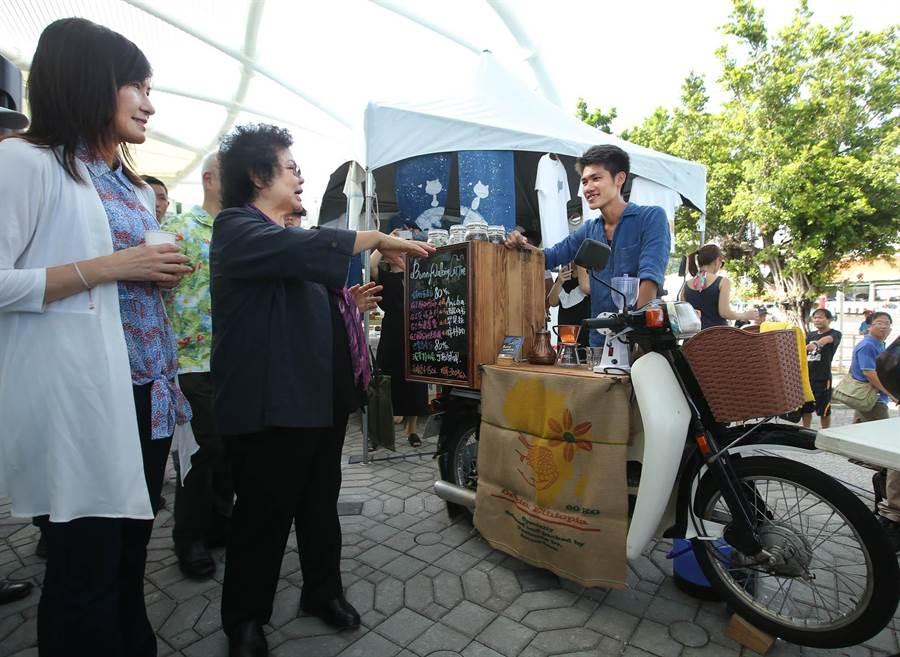 高雄市長陳菊(左二)在觀光局長曾姿雯(左)等人士陪同下參觀每周六日在西子灣遊客中心旁舉辦的戶外市集,眾人正參觀行動咖啡機車。(王錦河攝)