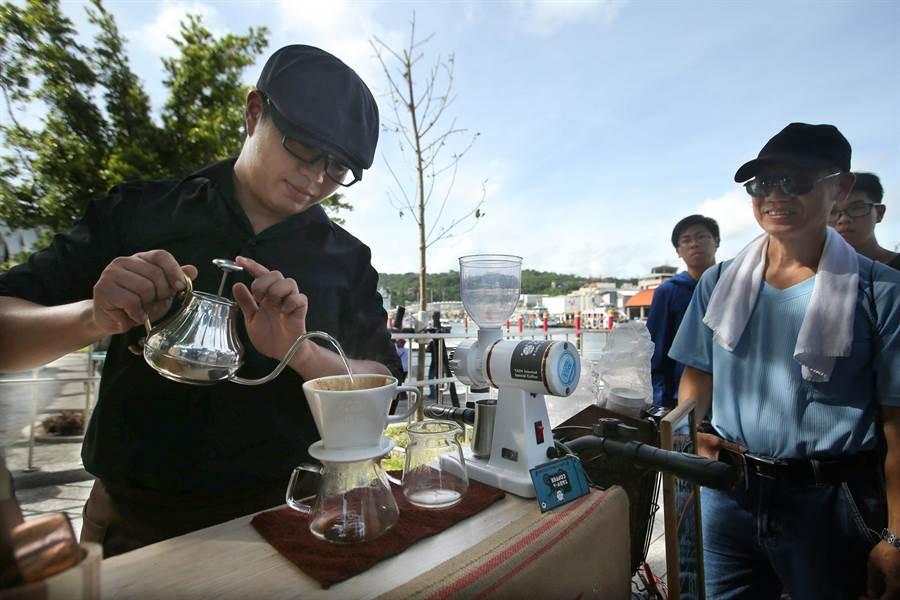 每周六日在西子灣遊客中心旁都會舉辦戶外市集至8月6日,行動咖啡車老闆正手沖咖啡,吸引民眾圍觀。(王錦河攝)