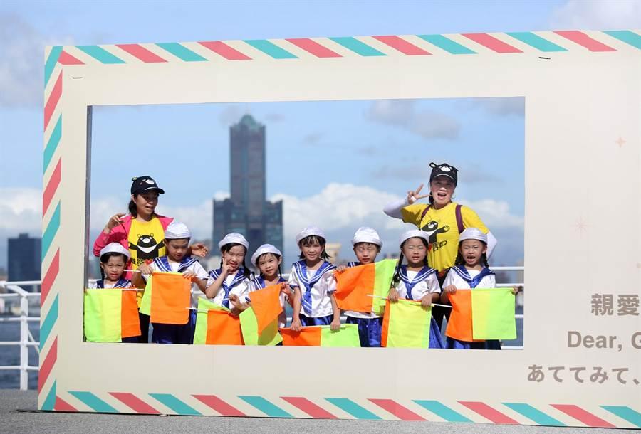 乖寶貝幼兒園園長蔡金定(右二)帶領小朋友一同在西子灣遊客中心海邊設置的大型信封拍照看板旁合影,背景就是高雄地標建築85大樓。(王錦河攝)