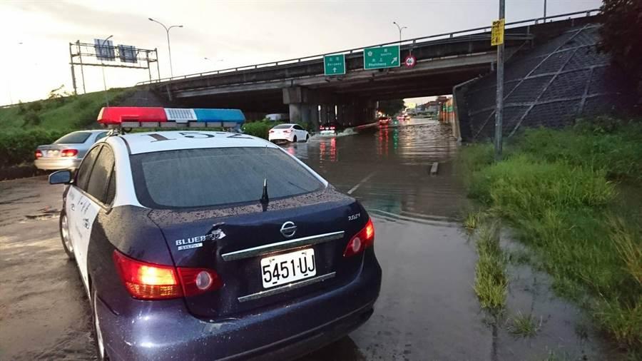 北港路外側車道及國道一交流道處淹水,無法通行車輛,警車駐地警戒。(廖素慧翻攝)