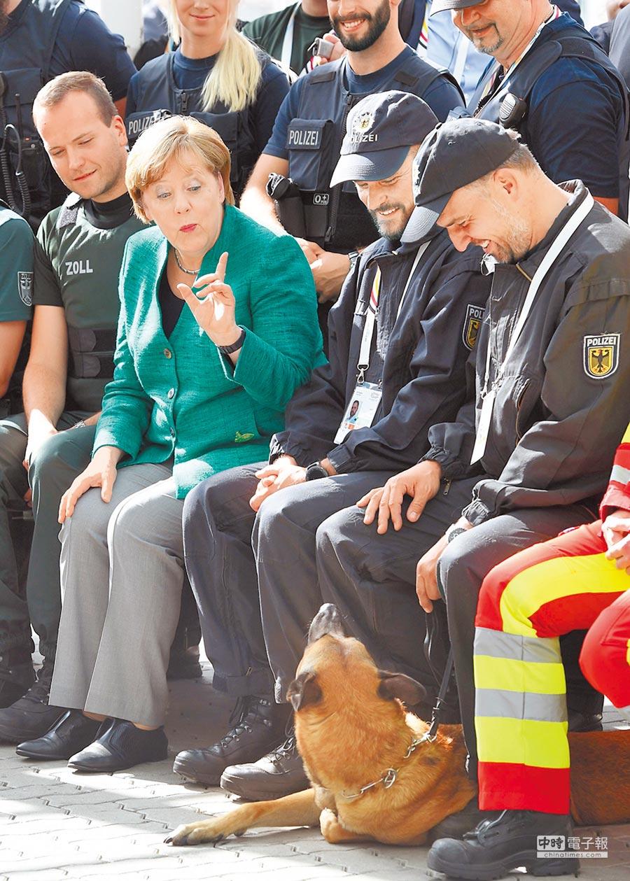 G20峰會閉幕,東道主德國總理梅克爾慰問員警,並對警犬「訓話」。(法新社)