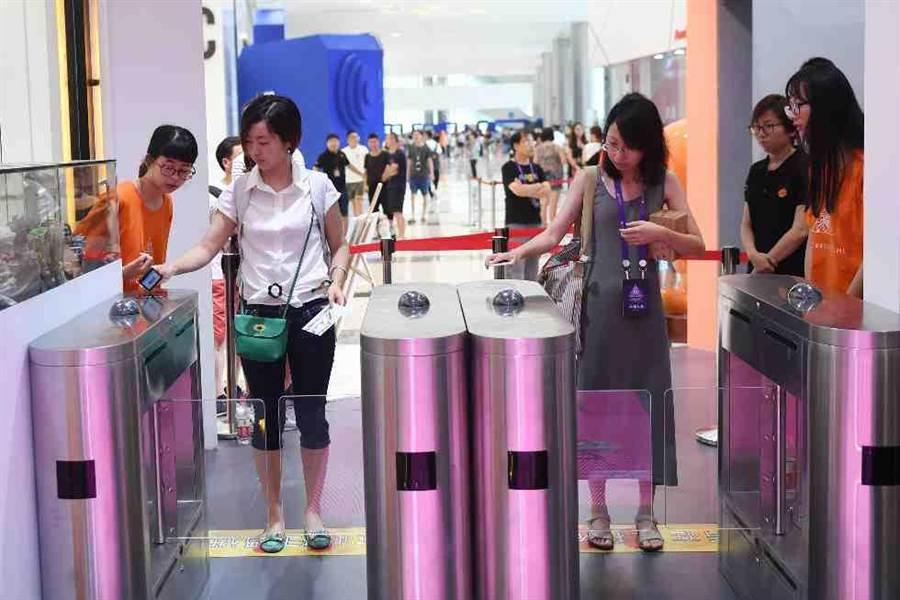 顾客使用手机扫码进入淘宝无人零售店。(新华社)
