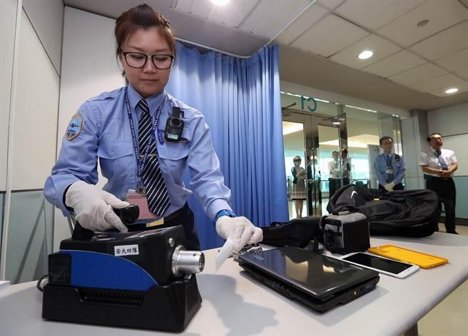 被抽中需進行二次安檢的赴美旅客,其隨身行李中攜帶的電子產品,將利用專用試紙一個一個每面都擦拭,再以「嗅覺式爆裂物偵測儀」立刻檢測,確認是否沾有爆裂物粉塵。(陳麒全攝)