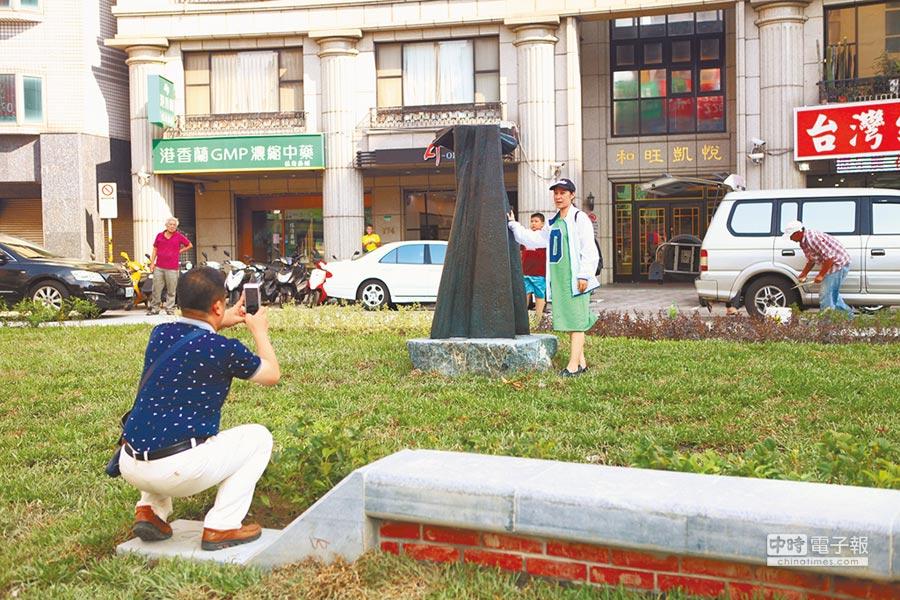 昨已有民眾為了已故雕刻大師楊英風的作品「龍穴」慕名而來,爭相合影留念。(張立勳攝)