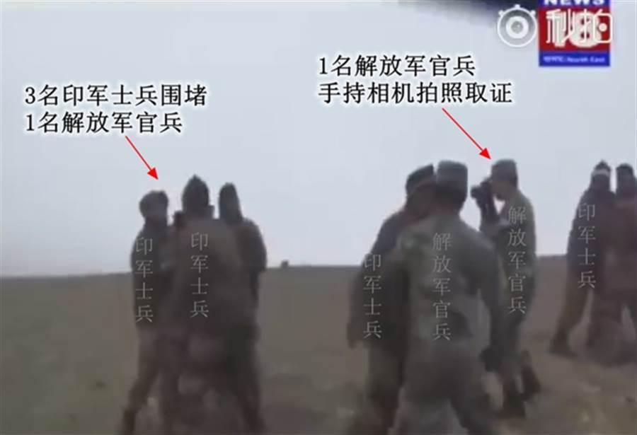 3名印度士兵圍堵1個解放軍官兵,1名解放軍官兵則手持相機拍照取證。(新浪軍事/印度電視台視頻截圖)
